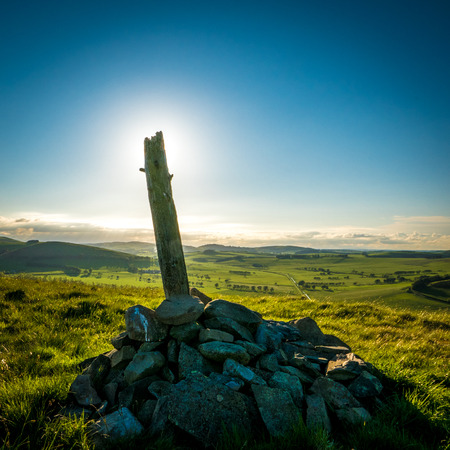 Stones And A Wooden Post At The Summit Of A Hill In Rural Scotland At Sunset