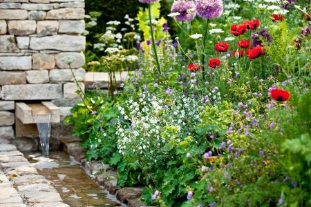 Garden flowers with stone walled stream