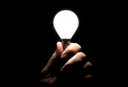 Lit lightbulb held in hand on black background