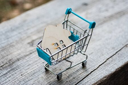 Photo pour Toy wooden house with a shopping trolley on a natural wooden background. Concept photo about buying real estate in nature or outside the city. - image libre de droit