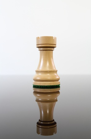 Tan wooden chess castle on a reflective glass table.