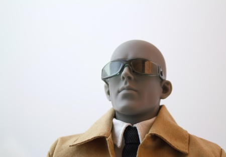 Portrait of a focused business male anatomical artist manikin with sunglasses and a coat.