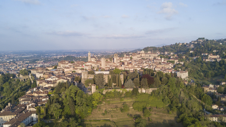 Drone aerial view of Bergamo - Old city (upper town), Italy. Landscape on the city center, the old fortress and its historic buildings during a wonderful blue day