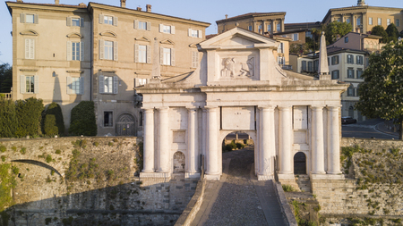 Bergamo - Old town. One of the beautiful cities in Italy. Aerial shot of the old gate named Porta San Giacomo during sunrise and a wonderful blue day