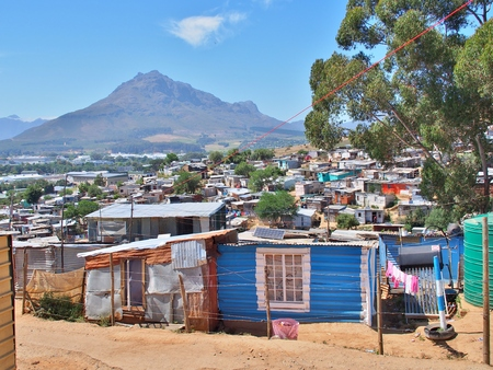 Photo pour Informal settlement - Enkanini with mountain and blue sky on the outskirts of Stellenbosch, Western Cape province, South Africa. Many shacks in Enkanini have solar panels for access to electricity. - image libre de droit