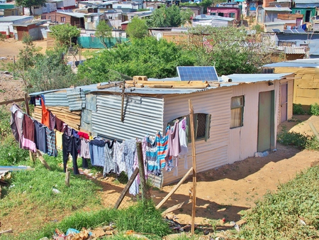 Solar panels on the roof of shack at Informal settlement - Enkanini, on the outskirts of Stellenbosch, Western Cape, South Africa. Many shacks in Enkanini have solar panels for access to electricity.