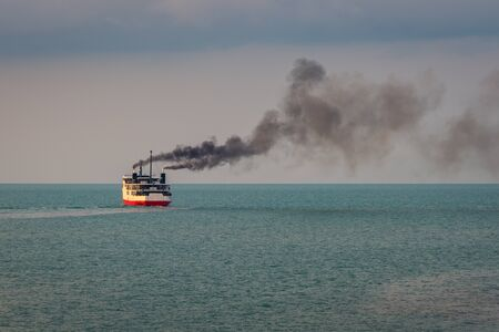 Huge boat or ferry with dark smoke float on the ocean at sunset time
