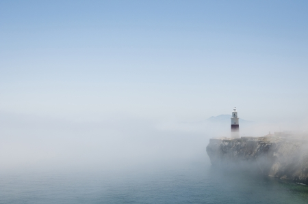 Gibraltars lighthouse at Europa Point standing in the mist with Africa in the distance.