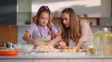 Attractive woman teaching girl to prepare dough for cookies on modern kitchen. Small daughter kneading dough with mother on kitchen in slow motion. Pretty child cooking with mom