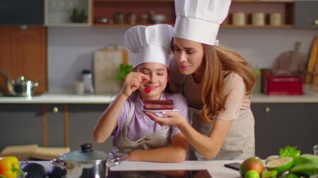 Close up small confectioner and mother putting cherry on cake at modern kitchen. Mother kissing daughter at home in slow motion. Two bakers in cooker uniforms smiling at camera on kitchen