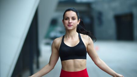 Portrait fit woman doing jump exercise with skipping rope outdoor. Close up athlete woman jumping on skipping rope in slow motion. Sporty girl finishing cardio exercise with jump rope.
