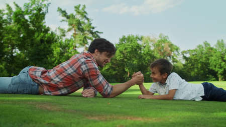 Photo pour Positive father and son lying on green grass in field. Side view happy boy and man competing in arm wrestling in park. Excitement boy celebrating victory outdoors. Happy family enjoying time in meadow - image libre de droit