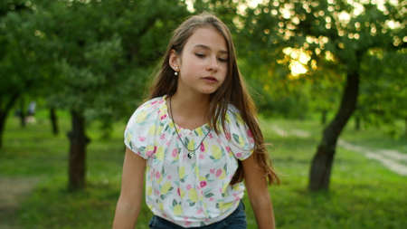 Photo pour Serious teenage girl dancing outside. Concentrated teen girl singing song in summer park. Pretty girl making dance movements otdoors in slow motion. - image libre de droit