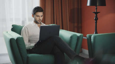 Photo pour Handsome businessman working laptop computer in luxury hotel. Business man working computer at remote workplace. Remote worker typing notebook at modern apartment. - image libre de droit