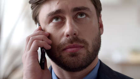 Photo pour Portrait of young businessman talking phone at remote office. Focused man discussing on cellphone in slow motion. Closeup handsome guy calling mobile phone at home office. - image libre de droit