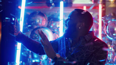 Photo pour Portrait of smiling male person doing selfie photo on neon lamps background. Closeup afro man showing victory sign under confetti in slow motion. African american man making photos at night club party - image libre de droit