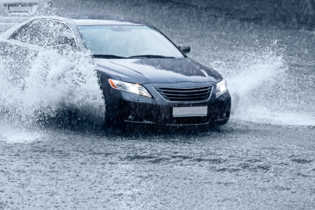 Car driving in city street after rain