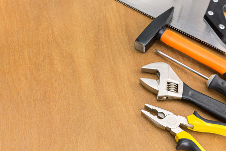 Workbench with different tools on wooden background
