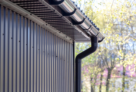 Photo pour brown siding wall with plastic rain gutter and drainpipe - image libre de droit
