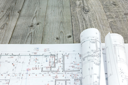 Photo for floor plan drawings with rolled architectural blueprints on wooden background - Royalty Free Image