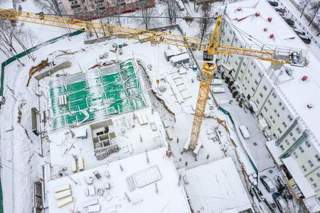 Photo pour reconstruction of apartment building in winter. tower crane working at construction site. top view - image libre de droit