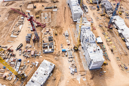 Photo pour aerial top view of construction site. tower cranes and other building machinery working at the building of new city apartments - image libre de droit