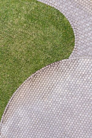 Photo for top view of gray cobblestone pavement footpath with green grass texture around stones - Royalty Free Image