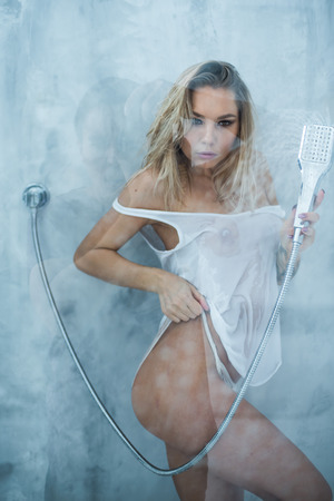 Photo pour A slender girl in a white wet t-shirt takes a shower, pours water on the glass. Window with water drops before girl. Rain drops on window glass with face of girl. Shower and hygiene spa treatment. - image libre de droit