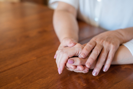 Photo pour Elderly mother and her daughter holding hands while sitting at the table.Close up on women of different generations holding hands. Close Up Shot Of Mother And Daughter's Hands Holding. - image libre de droit