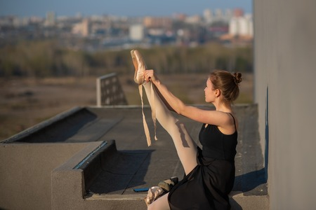 Foto de Ballerina in a tutu posing near the fence. Beautiful young woman wearing a black dress and wearing pointe shoes outside. Gorgeous ballerina demonstrates amazing stretching - Imagen libre de derechos