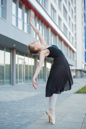 Foto per Ballerina in a tutu posing in front of a multi-storey residential building. Beautiful young woman in black dress and pointe shoes with incredible flexibility. Gorgeous ballerina performs an elegant backbeat. - Immagine Royalty Free