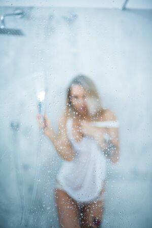 Photo pour A slender girl in a white wet t-shirt takes a shower, pours water on the glass. Window with water drops before girl. Rain drops on window glass with face of girl. Shower and hygiene spa treatment. Fashion and beauty. - image libre de droit