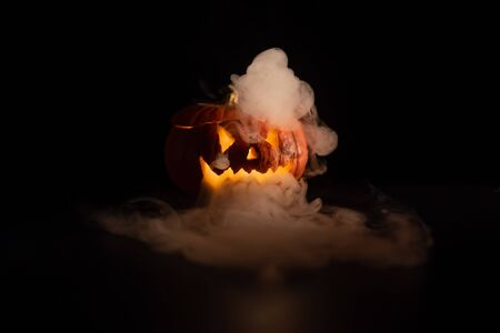 Foto de Halloween, orange pumpkin with a scary luminous face on a dark background. Gray thick smoke comes out. Close-up of jack-o'-lantern on the eve of all saints - Imagen libre de derechos