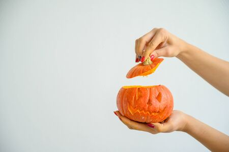 Photo pour Female hands holding a pumpkin for Halloween. Close-up of a woman opens the jack-o'-lantern cover on a white background on the eve of all the saints. front view - image libre de droit