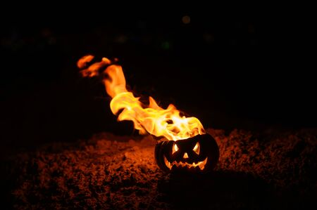 Foto de Tongues of flame in a pumpkin. jack-o-lantern on fire on a black background. Halloween symbol on the ground. Trick or treat. Close up. - Imagen libre de derechos