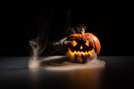 Foto de Halloween, orange pumpkin with a scary luminous face on a dark background. Gray thick smoke comes out. Close-up of jack-o-lantern on the eve of all saints. - Imagen libre de derechos