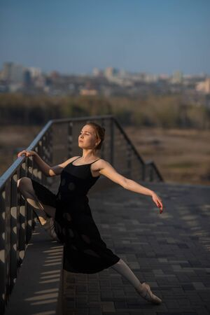 Foto per Ballerina in a tutu posing near the fence. Beautiful young woman in black dress and pointe dancing outside. Gorgeous ballerina demonstrates amazing stretching. - Immagine Royalty Free