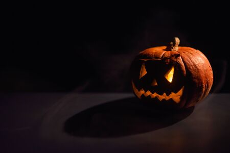 Foto de Halloween, orange pumpkin with a scary luminous face on a dark background. Thick gray smoke comes out and spreads across the black table. A close-up of a flashlight on the eve of all the saints - Imagen libre de derechos