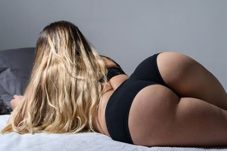 Photo pour A blonde with long hair in black underwear is lying on the bed. Rear view of a girl in thong sleeping on a gray plaid. A figured woman with wide hips, a big booty and a narrow waist. Close-up. - image libre de droit