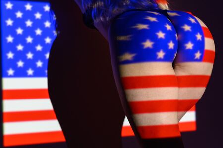 Photo for The projection of the flag of the United States of America on a beautiful large female ass. The projector shines with a flag on a female body. - Royalty Free Image