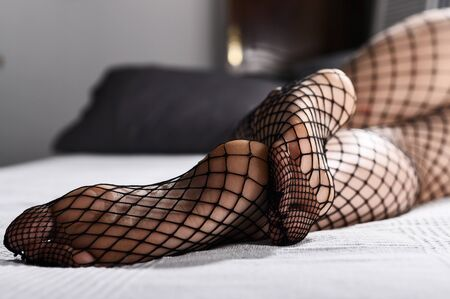 Foto de Female feet on the bed close-up. Legs of a girl in tights in a net. A woman in stockings lies on a sofa. - Imagen libre de derechos