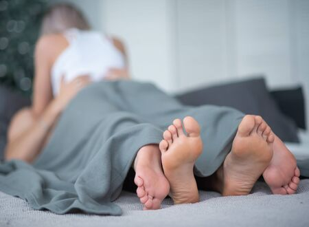 Photo pour Close-up of male and female legs. The loving couple lies and embraces on the bed under a gray blanket. Light room. - image libre de droit