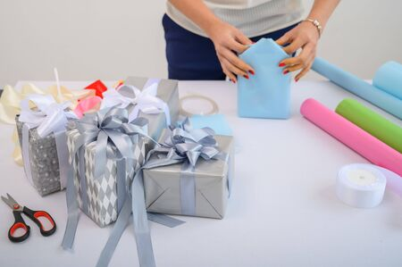 Foto de A woman wraps Christmas presents in wrapping paper and ties a ribbon bow. Close-up of woman's hands preparing surprises for the new year. Workflow of a derator. Desktop - Imagen libre de derechos