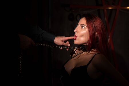 Foto de Portrait of a woman during role-playing games. A girl in fetters is in fetters in front of her lover and licks his fingers. A man touches his mistress by the face. - Imagen libre de derechos