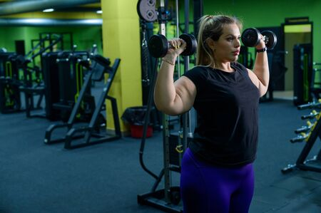 Photo pour An obese woman is working on losing weight. Fat blondes train biceps with a dumbbell in the trainer room. A lot of excess weight due to poor eating habits and lack of self-control. - image libre de droit