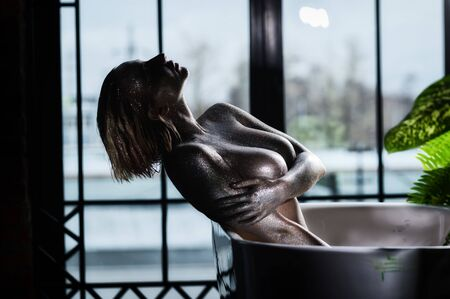 Photo for Nude woman with very large breasts with silver bodyart in the bathroom. A girl with an extra large bust with sparkles on her skin takes a shower. - Royalty Free Image
