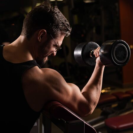 Photo for A handsome man with glasses doing an exercise for biceps with a barbell. The guy is engaged in bodybuilding. Trainer in the gym with muscular arms. - Royalty Free Image