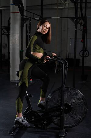 Photo pour Beautiful brunette with elastic buttocks exercises on an air bike. Athletic woman is engaged in the gym on an exercise bike. - image libre de droit