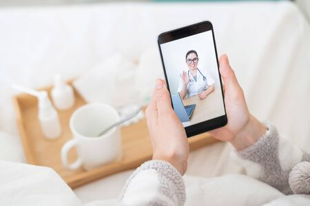 Foto de The concept of distance treatment. Rear view of a woman in bed in pajamas with a smartphone in her hands. A flu patient is watching a medical video blog. - Imagen libre de derechos