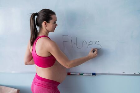 Photo pour A pregnant woman in sportswear writes the word fitness on a white marker board. A girl in the 3rd trimester goes in for sports with a bare tummy. Courses for expectant mothers. - image libre de droit